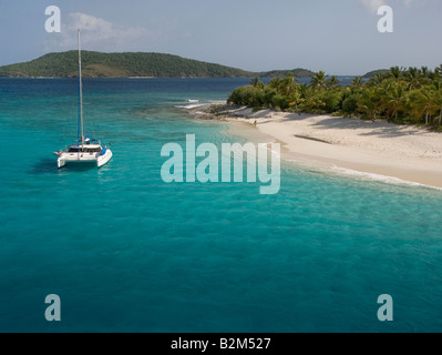 A cruising catamaran anchored next to uninhabited Sandy Cay in the British Virgin Islands. - Stock Photo