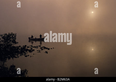 Sunrise in fog on Lake Cassidy Snohomish County two fishermen in small boat silhouetted fishing Washington State - Stock Photo