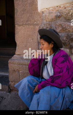 A peruvian lady sits thinking on the steps in Cusco, Peru - Stock Photo