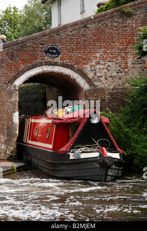 canal narrowboat exiting bridge number 46 bumble hole lock on the staffordshire and worcestershire canal wombourne - Stock Photo