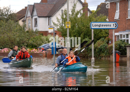 A FAMILY USING CANOES TO NAVIGATE FLOODWATER IN TEWKESBURY ROAD SANDHURST GLOUCESTER UK JULY 2007 - Stock Photo