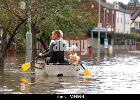 A FAMILY USE A ROWING BOAT TO NAVIGATE FLOODWATER IN TEWKESBURY ROAD SANDHURST GLOUCESTER UK JULY 2007 - Stock Photo