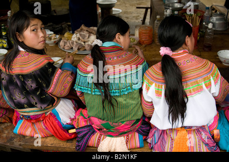 Three Flower Hmong tribe girls sitting at a food stall with backs to camera one looks over her shoulder at camera - Stock Photo