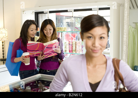 Portrait of a young woman in jewelry store with friends in the background - Stock Photo