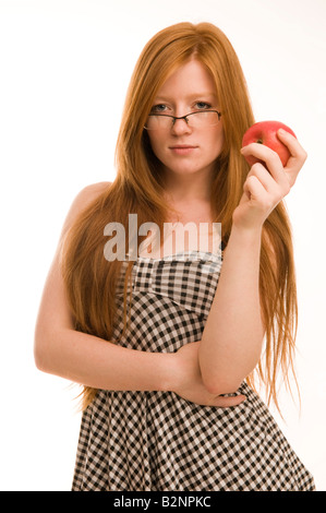 Red haired 19 year old slim pretty teenage girl holding apple  wearing glasses, long tresses hair, white background - Stock Photo