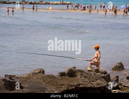 Costa Blanca Spain Alicante city woman fishing from the rocks Playa del Postiguet - Stock Photo