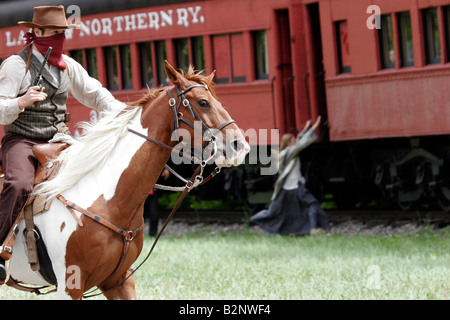 A cowboy bandit robbing an old steam train with a civilian girl trying to escape - Stock Photo