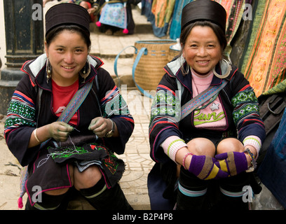 Two black Hmong tribe women wearing traditional costume smiling at the viewer in Sapa Vietnam - Stock Photo