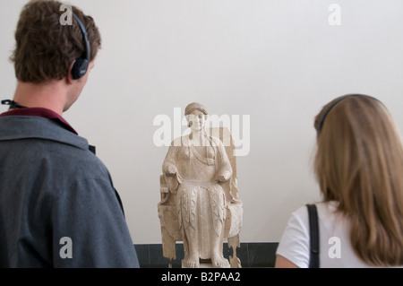 Visitors looking at ancient Greek relic and wearing headphones for audio guide system tour in Pergamon Museum in - Stock Photo