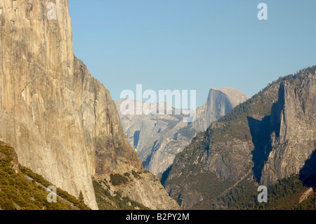 Granite walls of Yosemite Valley lit by warm late afternoon sun with Half Dome in the distance shot from Tunnel - Stock Photo