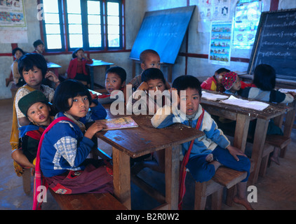Myanmar Burma Shan State Kalaw District Village of Myindaik young schoolchidren sitting on classroom bench - Stock Photo