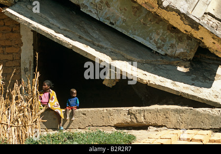 Mother and son sitting on destroyed building, Luanda, Angola - Stock Photo