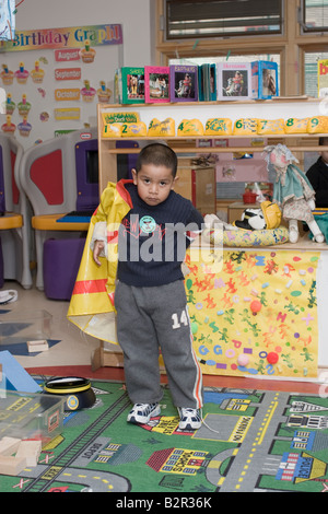 4 year old preschool boy putting on a policemans raincoat playing dressup - Stock Photo