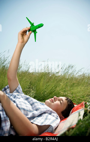 Boy lying down playing with plane - Stock Photo