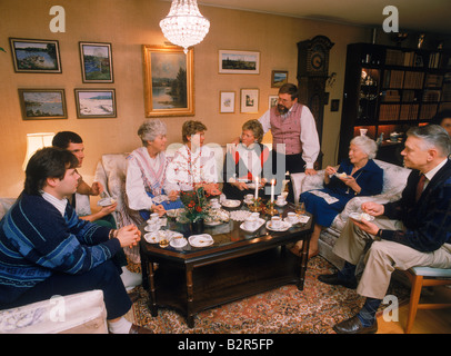 Family sharing food, coffee and conversation in frontroom of typical apartment in Stockholm - Stock Photo