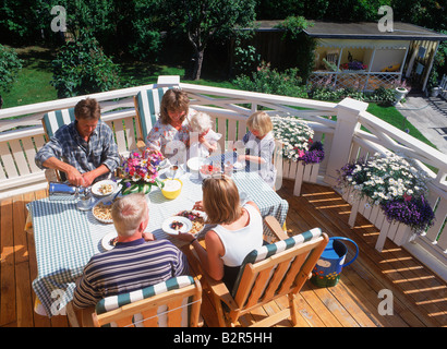 Friends sharing food, coffee and conversation on balcony of Swedish family home in summer - Stock Photo