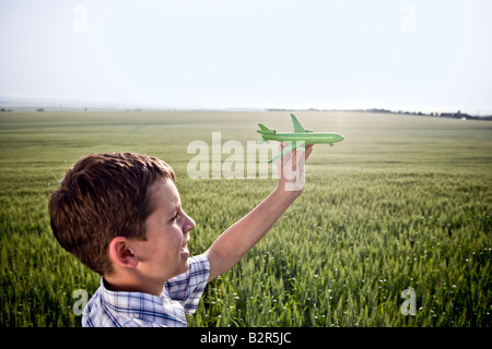 Boy playing with toy plane - Stock Photo