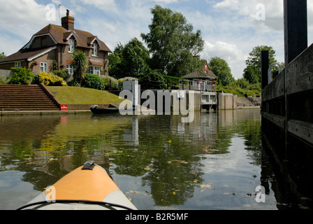 Kayak entering Old Windsor Lock, with lockeepers cottage and portage stairs, River Thames, Berkshire, England - Stock Photo