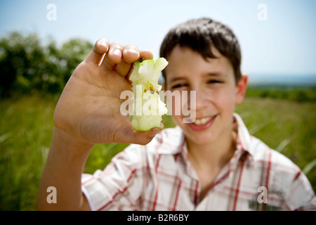 Boy holding up apple core - Stock Photo