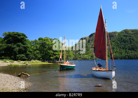 Green and white sailing boats with red sail moored on in a bay on Ullswater, The Lake District National Park, Cumbria, - Stock Photo