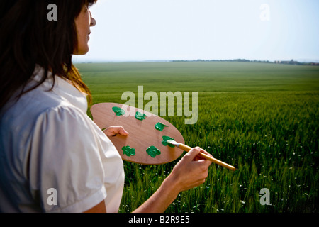 Woman holding painters palette - Stock Photo