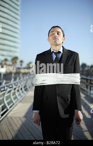 Business man tied up with ropes outdoors - Stock Photo