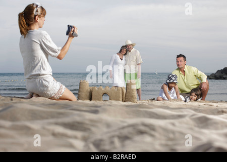 Mother taking video of family on beach - Stock Photo