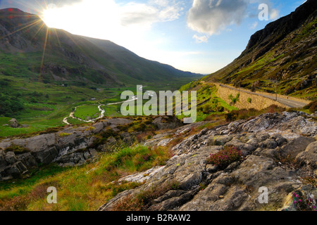 The Nant Ffrancon Pass in Snowdonia North Wales looking directly towards the late evening sun as it recedes behind - Stock Photo