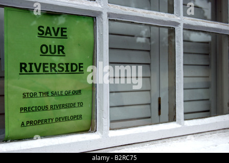 green sign with black text on a residential window in twickenham, england, opposing the dsale of riverside land - Stock Photo