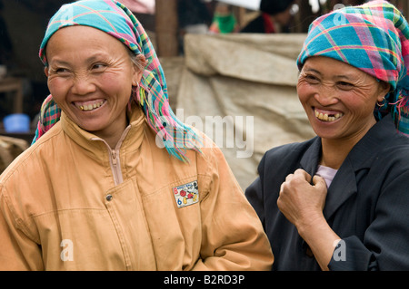 Two old flower Hmong women wearing traditional head scarfs laughing in a market Vietnam - Stock Photo