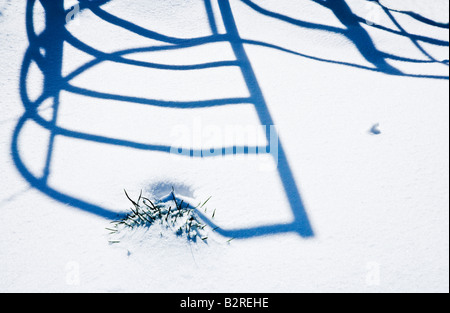 Shadow patterns on snow cast by a wrought iron kissing gate - Stock Photo