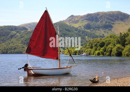 White sailing boat with red sails moored on in a bay on Ullswater, The Lake District National Park, Cumbria, England. - Stock Photo