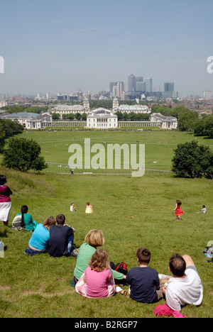 Tourists in Greenwich Park. View to Royal Naval College, National Maritime Museum and Canary Wharf - Stock Photo