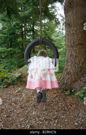 young girl wearing pretty dress outside in nature swinging backward on tire swing. child is seen from rear or back - Stock Photo