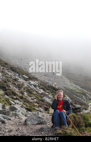 A man talks on the phone on his descent from the top of Croagh Patrick, County Mayo, Ireland - Stock Photo
