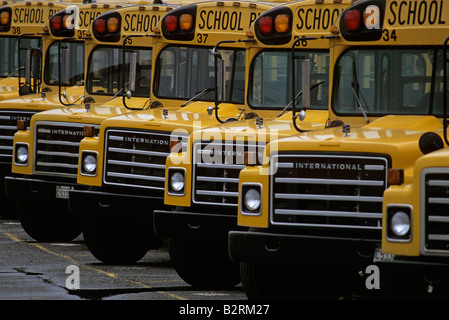 Row of yellow school buses in bus depot - Stock Photo