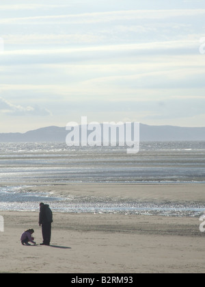 father and kid on beach in rhyl north wales - Stock Photo