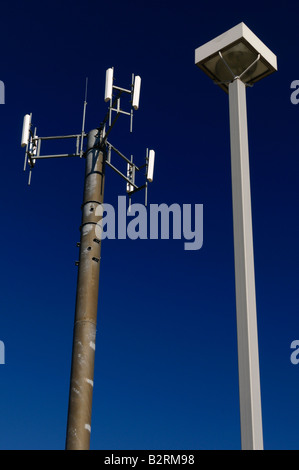 Cell phone communications tower against a blue sky with a lamp post - Stock Photo