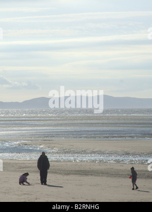father and kids on beach in rhyl north wales - Stock Photo