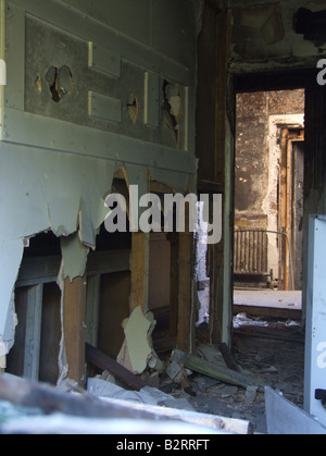 inside vandalised dark room in abandoned derelict property - Stock Photo