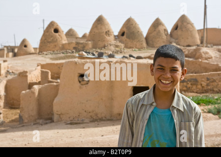 Arab Boy in front of Ancient Beehive Houses in Syria - Stock Photo
