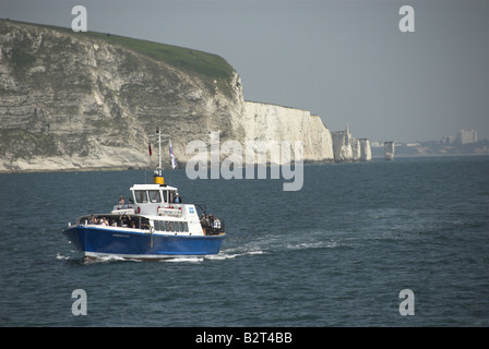 Pleasure craft taking tourists sightseeing along the coast of Dorset with cliffs and old Harry rocks in Background - Stock Photo
