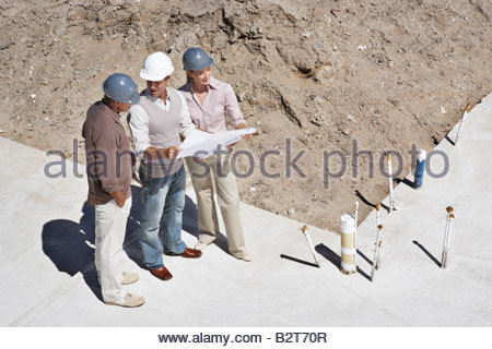 Construction workers viewing blueprints on construction site - Stock Photo