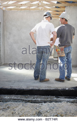 Construction workers reviewing blueprints at construction site - Stock Photo