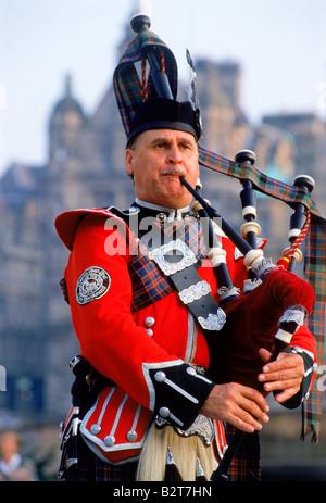 Bagpiper playing near Scott Monument at city center of Edinburgh, Scotland - Stock Photo