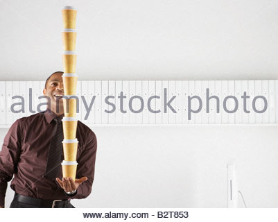 Businessman balancing large stack of paper coffee cups - Stock Photo
