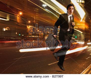 Businessman running with light streaking around him - Stock Photo