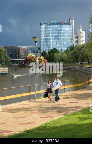 Young couple walking on Mother River ( Emajogi ) promenade modern buildings in the background. Tartu Estonia Europe - Stock Photo