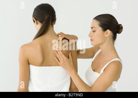 Massage therapist giving woman shoulder massage - Stock Photo