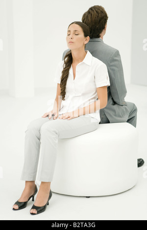 Two professionals sitting back to back on ottoman, woman's eyes closed - Stock Photo